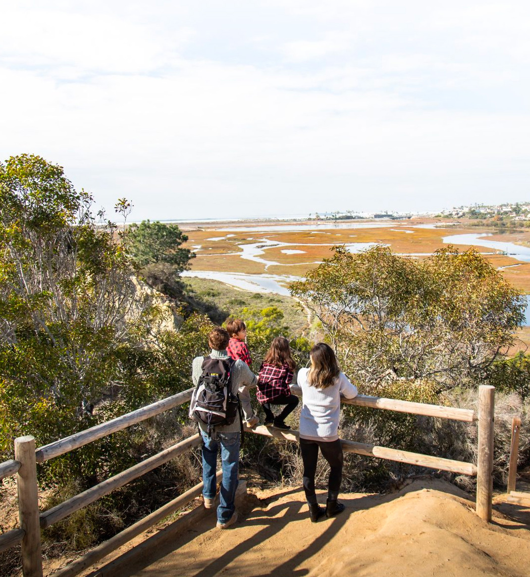 Man, woman and two children overlook the lagoon from the top of Annie's canyon trail